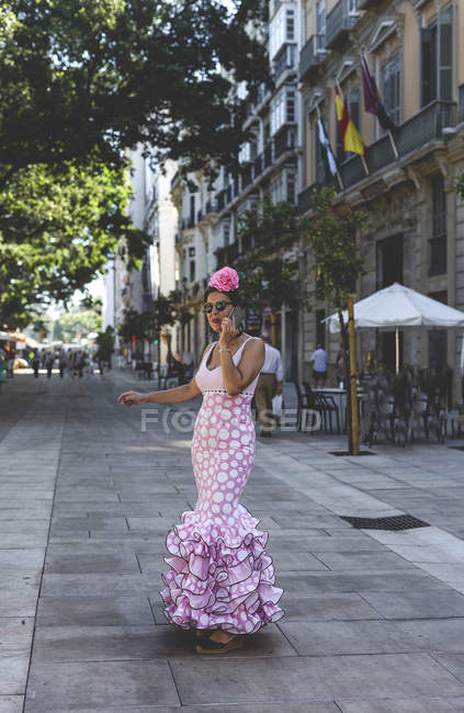 Eccentric woman in colorful pink costume speaking on smartphone while walking along summer street — стокове фото