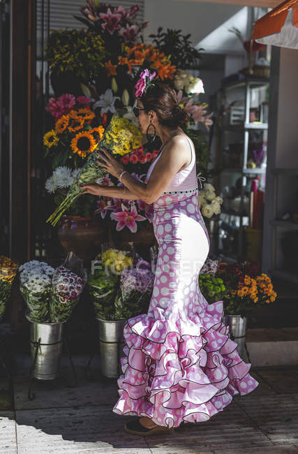 Side view of eccentric curious woman in colorful pink costume picking beautiful bright bouquet at flower shop on sunny day — Stock Photo
