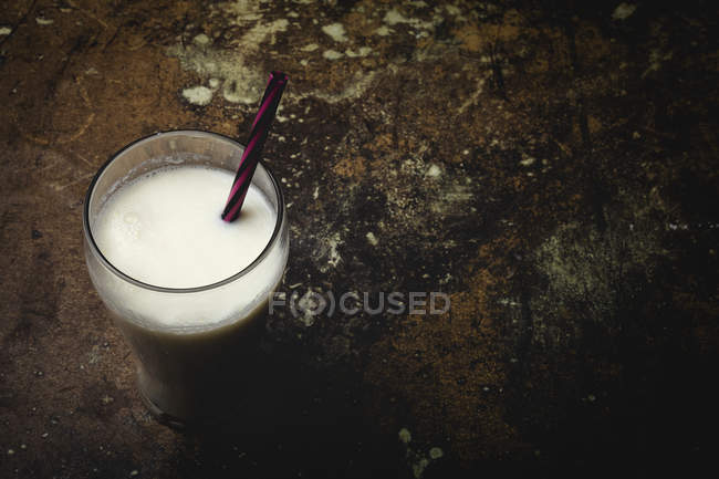 Hohes Glas weißer Milch mit hell gestreiftem Stroh auf Tisch über schwarzem Hintergrund — Stockfoto