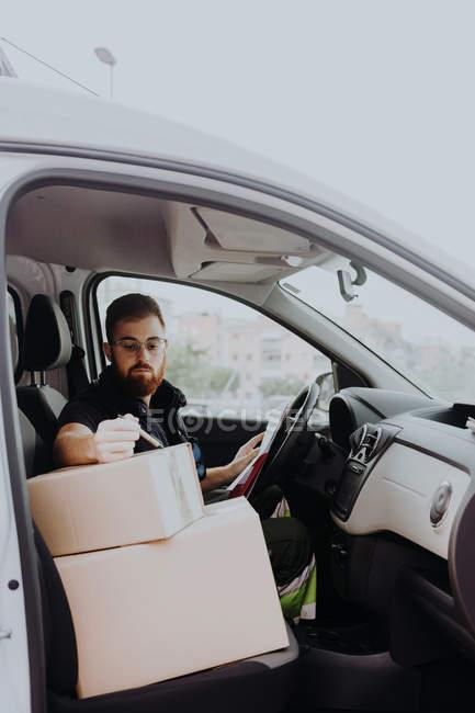 Курьер в очках готовит пакеты для транспортировки во время сидения и маркировки коробок в автомобиле на размытом фоне в дневное время — стоковое фото