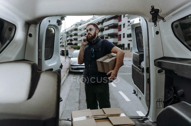 Курьер в очках держит коробки и делает предупреждение клиенту для дальнейшей доставки, стоя возле багажника автомобиля и глядя в сторону в дневное время — стоковое фото