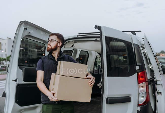 Курьер в очках аккуратно разгружает картонные коробки из автомобиля для дальнейшей доставки клиенту на размытом фоне в дневное время — стоковое фото