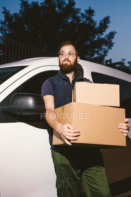 Взрослый бородатый мужчина в очках думает и смотрит в сторону, стоя возле машины и держа картонные коробки вечером — стоковое фото