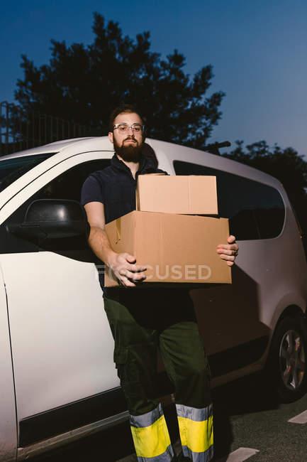 Взрослый бородатый мужчина в очках думает и смотрит в камеру, стоя возле машины и держа в руках картонные коробки вечером — стоковое фото
