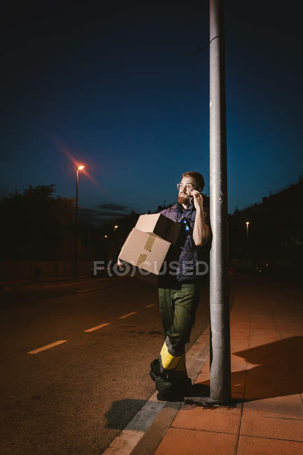 Adult bearded courier in glasses with boxes making warning call and looking away while standing and leaning on streetlight post on street in evening — Stock Photo
