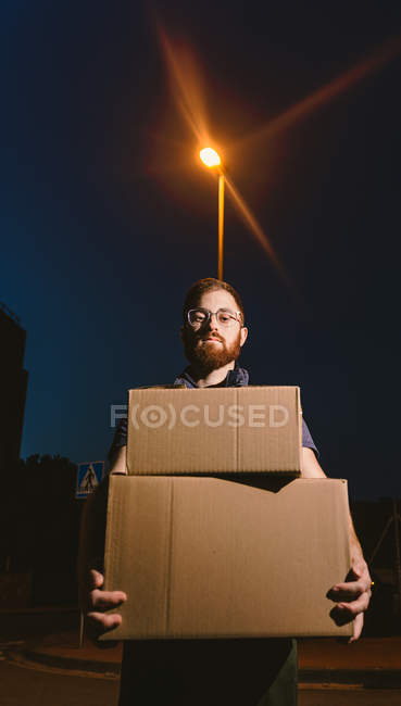 Homme dans des lunettes portant des boîtes tout en se tenant sur la rue et en regardant la caméra près du lampadaire lumineux dans la soirée sur fond flou — Photo de stock