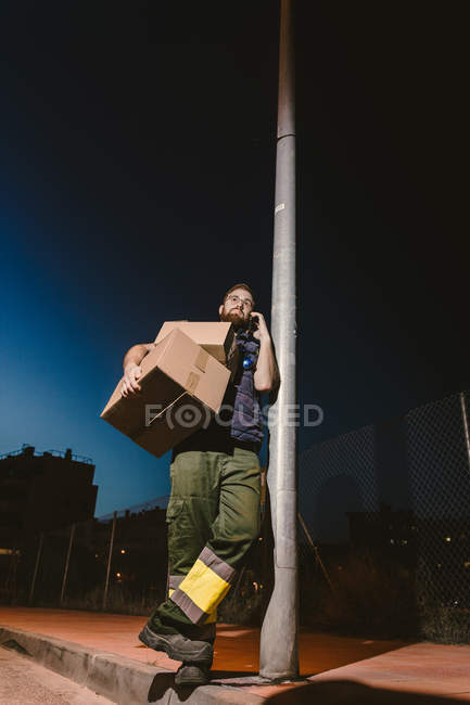 Courier in glasses with boxes making warning call while standing and leaning on streetlight post on street in evening — Stock Photo
