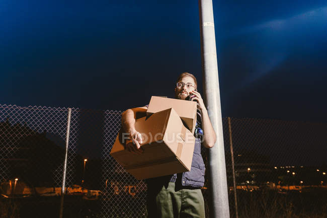 Courier in glasses with boxes making warning call to customer for further delivery and looking away while standing and leaning on streetlight post on street in evening — Stock Photo