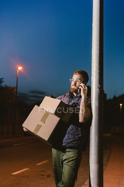 Courier in glasses with boxes making warning call and looking away while standing and leaning on streetlight post on street in evening — Stock Photo