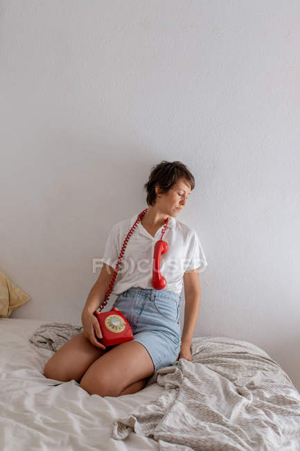Woman with handset of red telephone near ear listening while sitting on bed against white wall in bedroom — Stock Photo