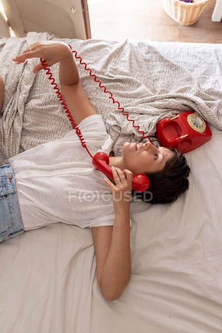 Femme répondant à l'appel téléphonique du téléphone rouge vintage tout en étant couché sur le lit dans une chambre confortable — Photo de stock