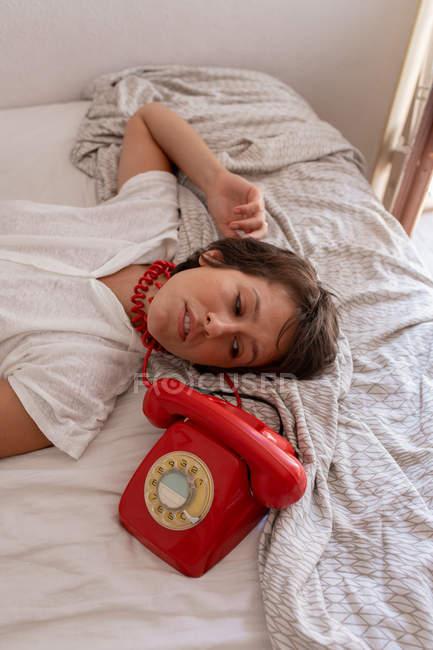 Сверху депрессивная женщина с красным телефоном рядом с головой смотрит вверх во время телефонного разговора на кровати — стоковое фото