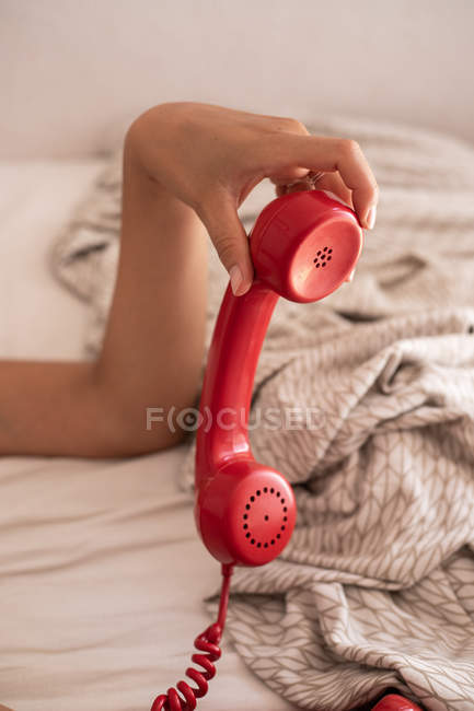 Image recadrée de la femme jouant avec le combiné rouge sur le téléphone rétro après avoir terminé la conversation sur le lit — Photo de stock