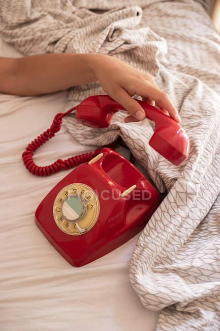 Обрезанное изображение женщины, надевающей красный телефон на ретро-телефон после окончания разговора на кровати — стоковое фото