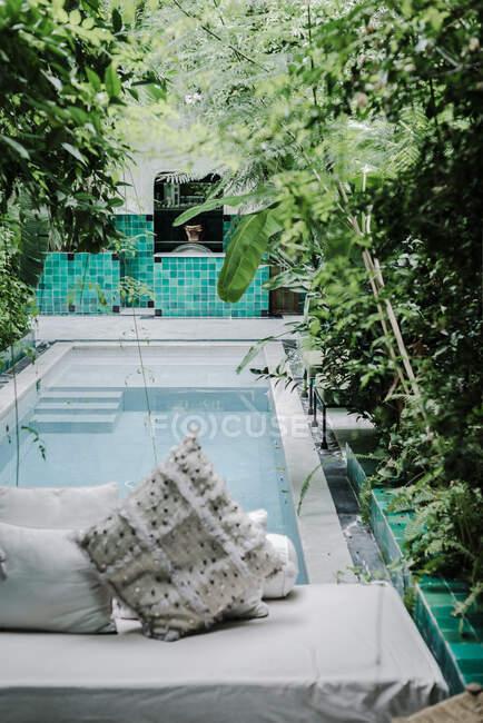 Morbida panca con cuscini situata vicino alla piscina pulita nel giardino verde dell'hotel a Marrakech, Marocco — Foto stock