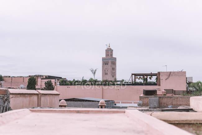 Alta torre araba tradizionale situato in mezzo alla strada contro cielo nuvoloso a Marrakech, Marocco — Foto stock