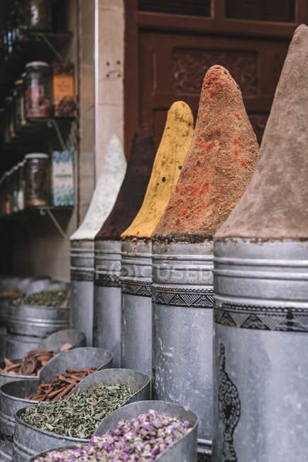 Especiarias aromáticas variadas em recipientes de metal colocados em baia no mercado na rua de Marraquexe, Marrocos — Fotografia de Stock