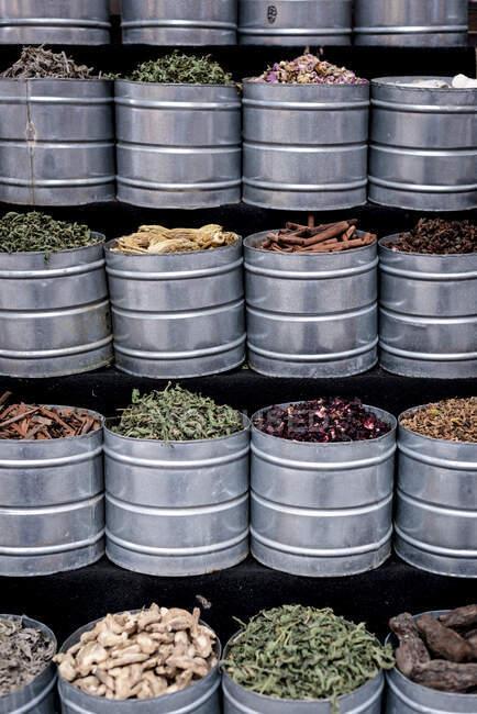 Vasi di metallo con spezie essiccate assortite situati in bancarella sul mercato di strada a Marrakech, Marocco — Foto stock