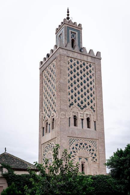 Da sotto alta torre araba con ornamenti tradizionali situato contro cielo nuvoloso sulla strada di Marrakech, Marocco — Foto stock