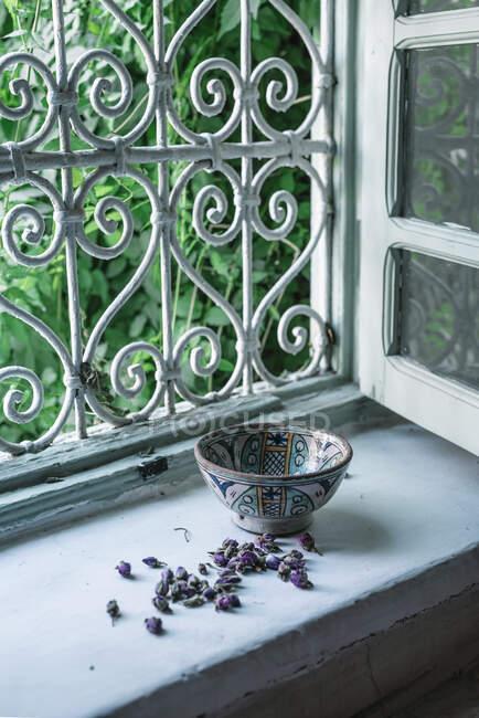 Pequenos botões de flores secas e tigela ornamental colocados perto da janela aberta dentro da casa árabe tradicional em Marraquexe, Marrocos — Fotografia de Stock