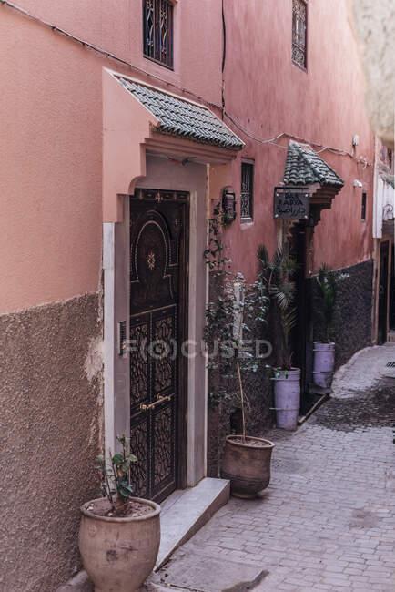 Vasos com plantas colocadas fora das portas do edifício pobre na rua de Marraquexe, Marrocos — Fotografia de Stock