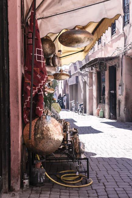 Utensílios de cozinha de cobre tradicionais brilhantes colocados fora da loja no dia ensolarado na rua de Marraquexe, Marrocos — Fotografia de Stock