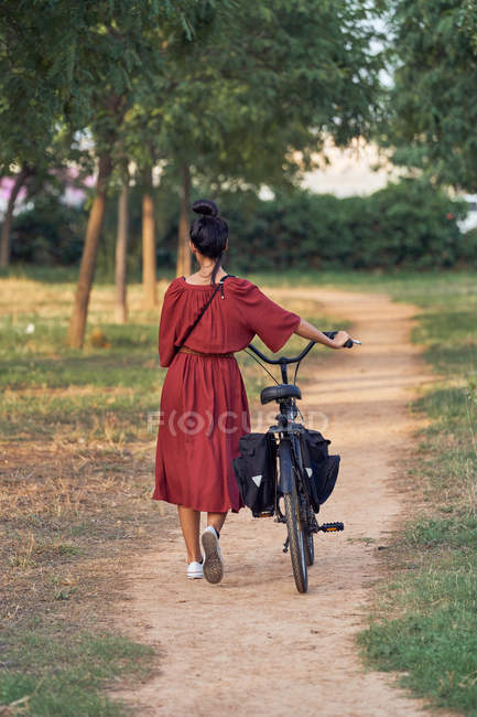 Back view of woman in dress pushing bike and smiling while walking along path on sunny day in park — Stock Photo