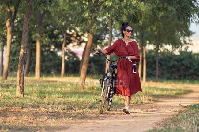 Woman in dress pushing bike and smiling while walking along path on sunny day in park — Stock Photo