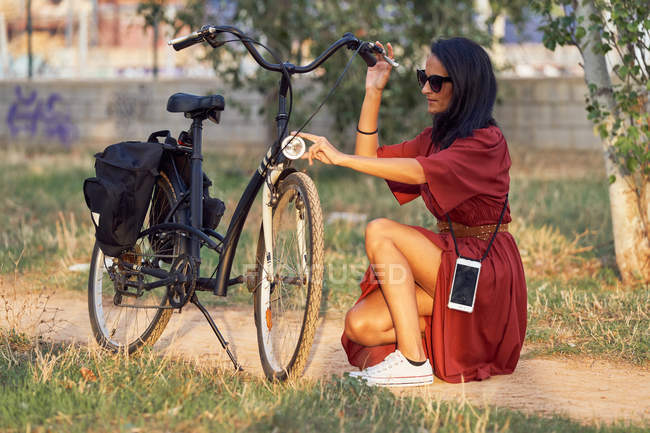 Side view of full length woman in dress repairing bicycle headlight while sitting on path in park — Stock Photo