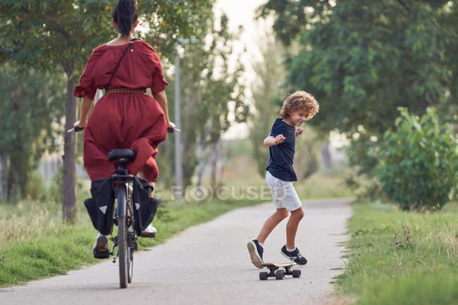 Konzentrierter Junge fährt Skateboard vor fröhlicher Frau auf Fahrrad auf Asphaltweg, während er Zeit im Park verbringt — Stockfoto