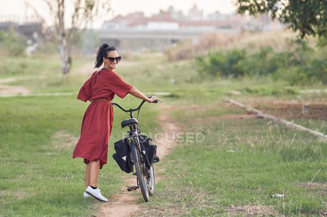 Вид сзади женщины в платье, толкающей велосипед и улыбающейся во время прогулки по дорожке в солнечный день в парке — стоковое фото