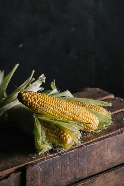 Организация свежих кукурузных початков на деревянном ящике — стоковое фото