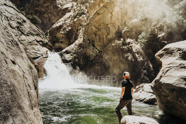 Side view of man in casual clothes contemplating water cascade surrounded with rocky slopes and mist on sunny day in USA — Stock Photo