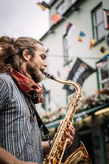Männlicher bärtiger und langhaariger Saxofonist spielt Saxofon mit heller Emotion auf der Straße — Stockfoto
