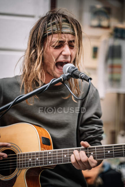 Portrait of expressive street musician playing guitar and singing with emotion — Stock Photo