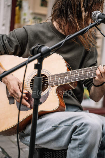 Unrecognizable street musician playing guitar, midsection — Stock Photo