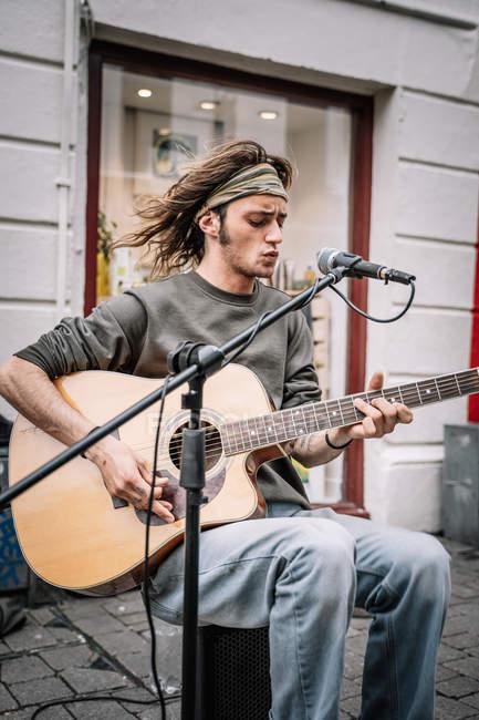 Musicista di strada espressivo che suona la chitarra e canta con emozione mentre siede al microfono — Foto stock