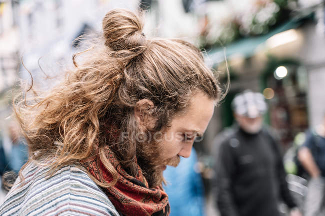 Portrait of pensive bearded and long-haired man in street looking down — Stock Photo