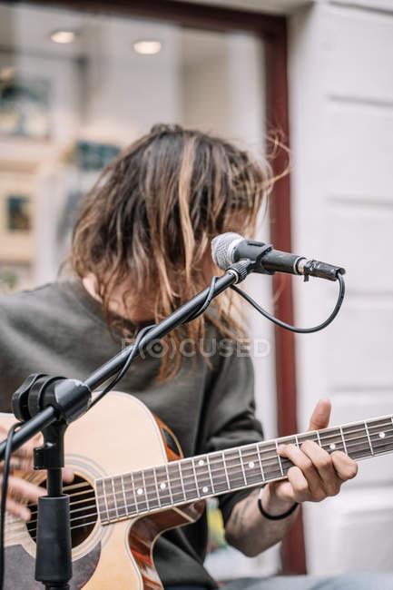 Musicista di strada maschile che suona la chitarra e canta per strada — Foto stock