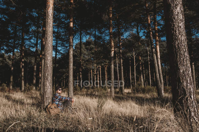 Relaxed tourist resting by tree in forest — Stock Photo