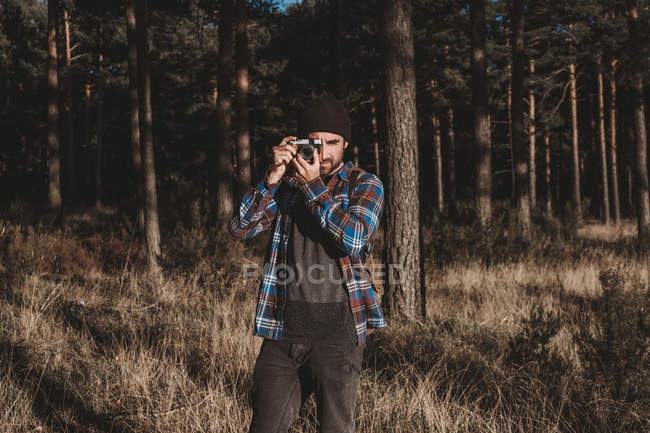 Uomo barbuto in abito casual scattare foto con macchina fotografica mentre in piedi circondato da alberi sempreverdi — Foto stock