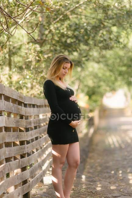 Pregnant woman looking down and touching belly while standing on road near garden in sunny day — Stock Photo