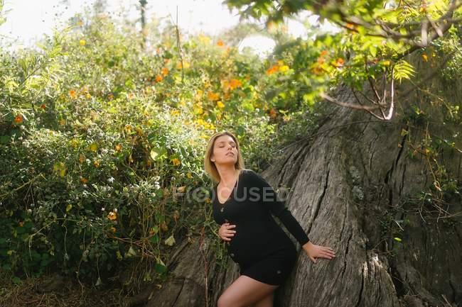 Беременная женщина сидит в саду в солнечный день — стоковое фото