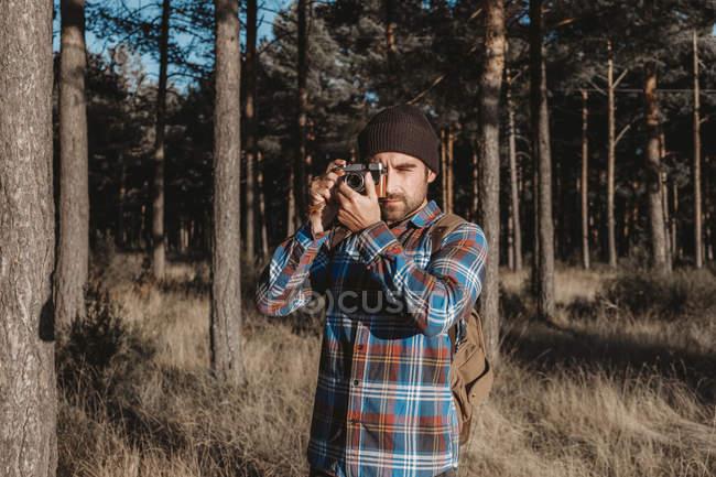 Уверенный фотограф фотографируется с камерой в солнечном лесу — стоковое фото