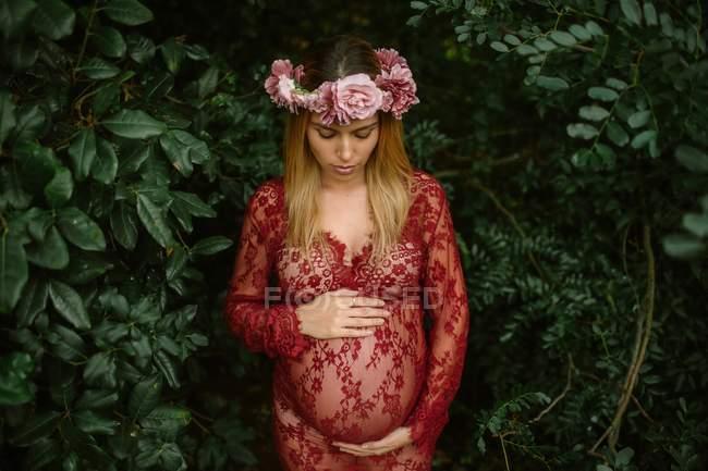 Беременная женщина с закрытыми глазами касается живота, стоя в саду в солнечный день — стоковое фото