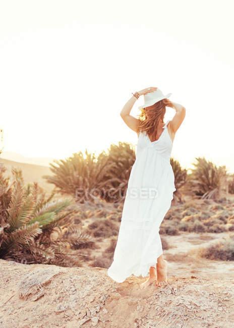 Женщина в белом платье трогает шляпу в сухом поле при солнечном свете — стоковое фото