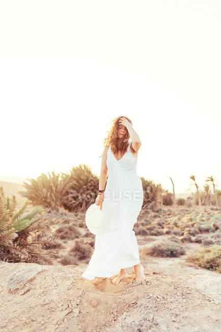 Mulher de vestido branco em campo seco à luz do sol — Fotografia de Stock