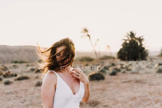Mulher de vestido branco com cabelos bagunçados em campo seco à luz do sol em Fuerteventura, Espanha — Fotografia de Stock