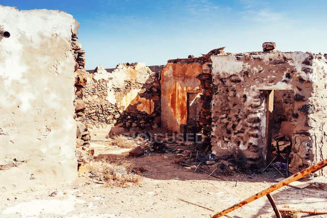 Обветшалые старые здания в горной пустыне под облачным небом — стоковое фото