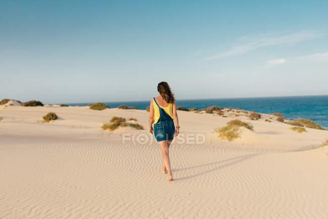 Active woman walking in dry desert sand barefoot — Stock Photo